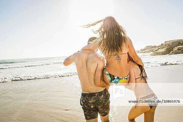 Rear view of couple carrying woman wearing bikini at beach,  Cape Town,  South Africa