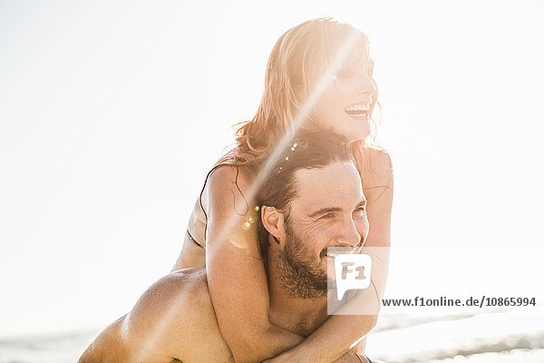 Mann schenkt Freundin Huckepack im Meer  Kapstadt  Südafrika