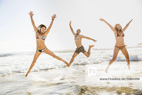 Drei erwachsene Freunde in Bikini und Shorts springen im Meer  Kapstadt  Südafrika