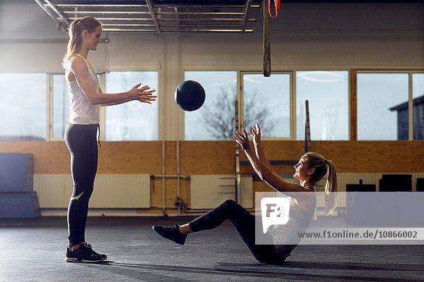 Zwei Crossfitterinnen werfen Medizinball im Fitnessstudio