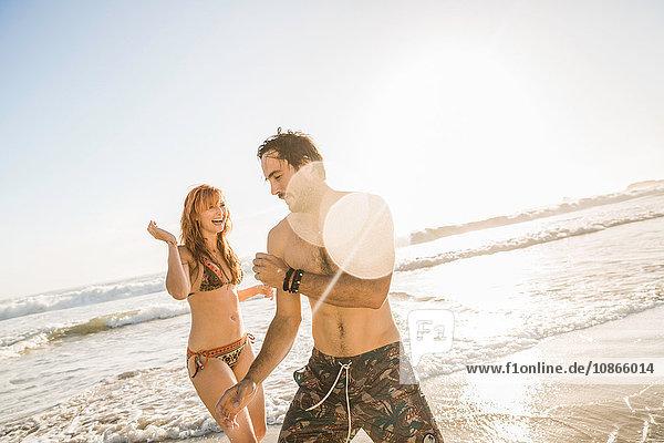 Mittlere erwachsene Frau im Bikini  die mit ihrem Freund am Strand spielt  Kapstadt  Südafrika