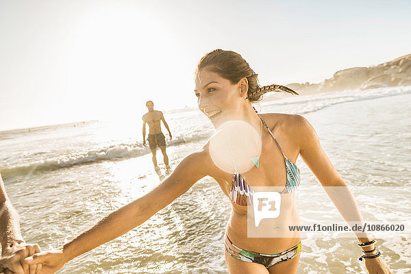 Mid adult woman wearing bikini playing with friends on beach  Cape Town  South Africa