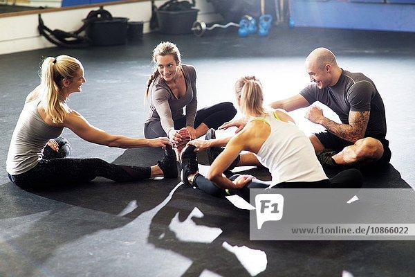 Männliche und weibliche Crossfitter sitzen im Kreis und berühren die Zehen