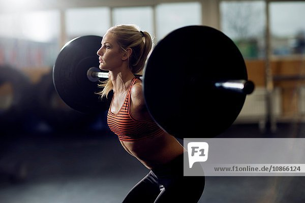 Mid adult female crossfitter lifting barbell on shoulders in gym