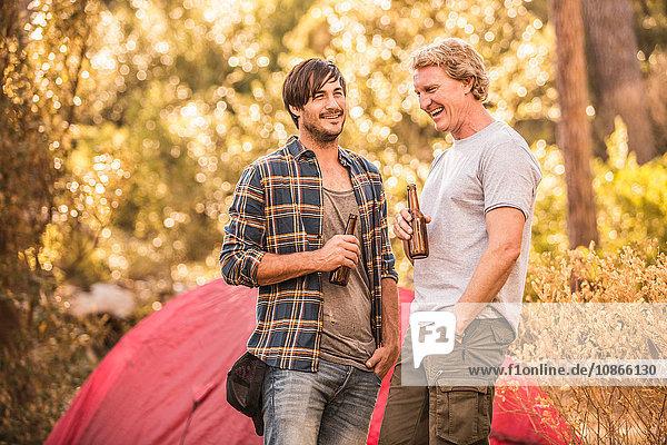 Zwei männliche Camper unterhalten sich und trinken Bier im Wald  Deer Park  Kapstadt  Südafrika
