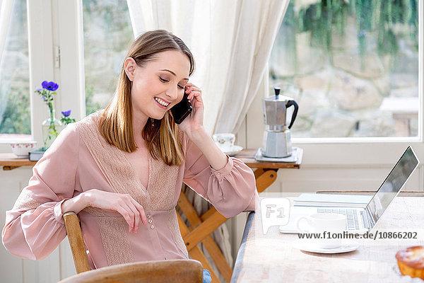 Frau sitzt am Tisch und telefoniert