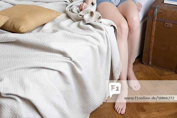 Beine der Frau auf dem Bett sitzend