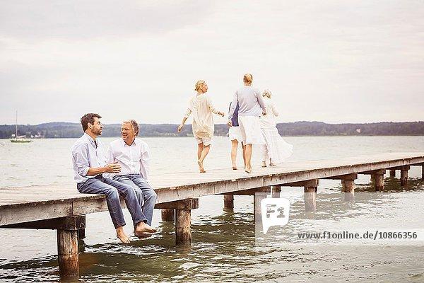 Zwei männliche Freunde sitzen am Rand des Piers und unterhalten sich  weibliche Freunde gehen auf das Ende des Piers zu
