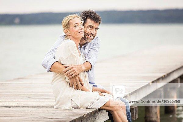 Reifes Paar  das am Rand des Piers sitzt und sich umarmt