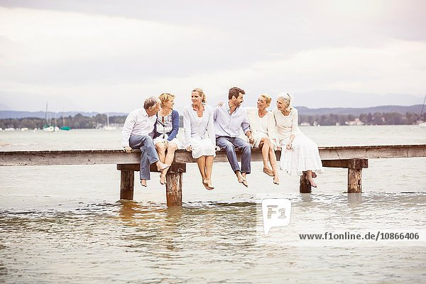 Gruppe von Freunden  die in einer Reihe am Rand des Piers sitzen