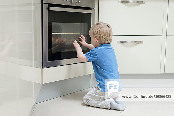 Young boy sitting in front of oven  looking through glass  rear view