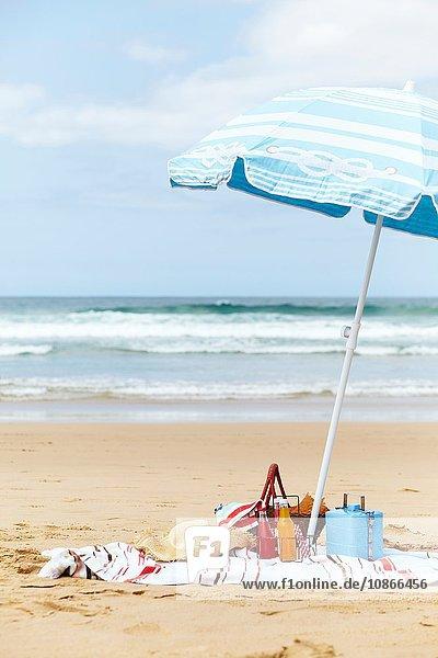 Sonnenhut  Kühlbox und Picknickkorb auf einem Strandtuch unter einem Sonnenschirm am Strand