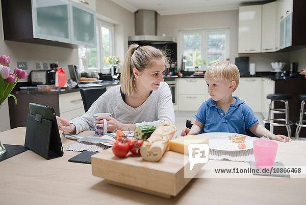 Mutter und Sohn sitzen gemeinsam am Tisch und essen zu Abend  der Sohn schaut auf das digitale Tablett