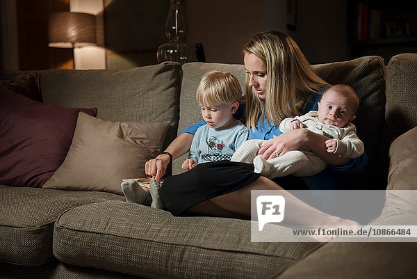Mother relaxing on sofa with son and baby boy