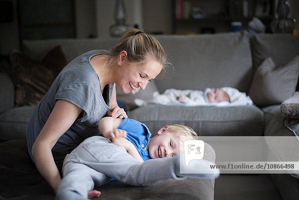 Mutter und Sohn albern im Wohnzimmer herum und lachen