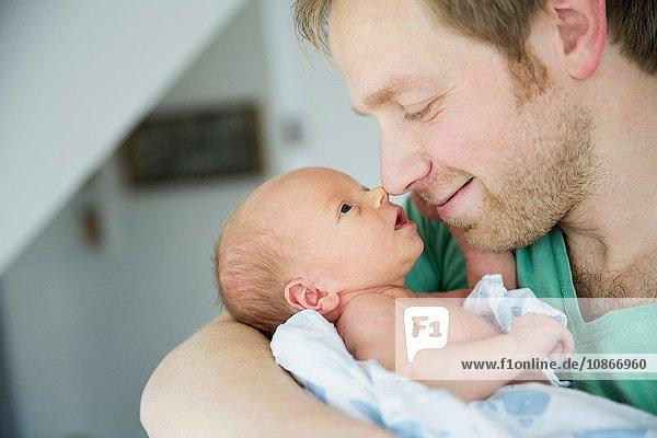 Vater wiegt Baby Junge  Nase an Nase lächelnd
