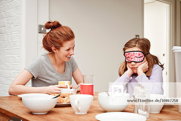 Mid adult woman at breakfast table with daughter wearing sleep mask