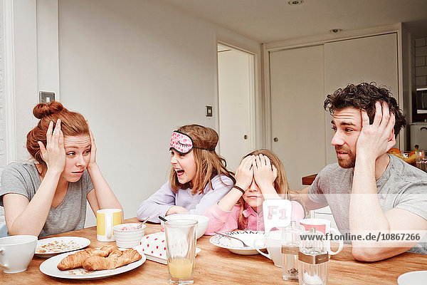 Tired mid adult parents at breakfast table with two daughters