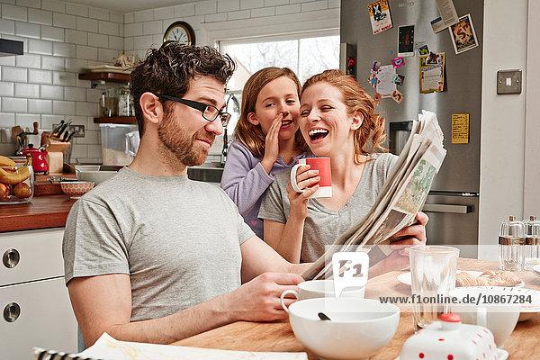 Mittelgroßer Mann am Frühstückstisch  der Zeitung liest  während Tochter und Mutter lachen