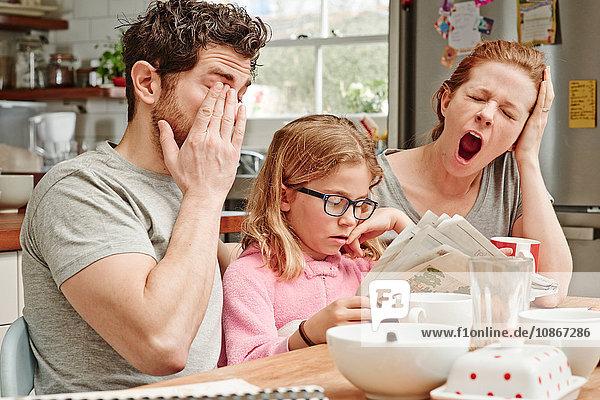 Müde  mittlere erwachsene Eltern am Frühstückstisch  während die Tochter Zeitung liest