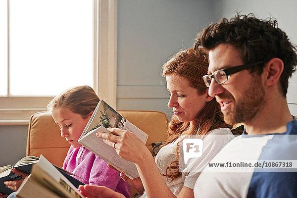 Mittlere erwachsene Eltern und Tochter auf dem Sofa beim Lesen von Büchern