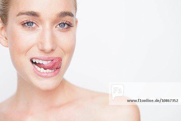 Ausschnitt einer Frau mit herausgestreckter Zunge  die lächelnd in die Kamera schaut