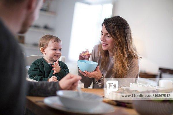 Eltern füttern am Esstisch lächelndes Baby