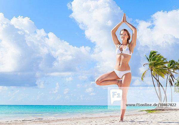 Young woman wearing bikini practising yoga tree pose on beach  Dominican Republic  The Caribbean