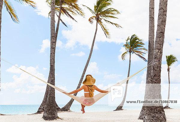 Rückansicht einer auf einer Strandhängematte sitzenden jungen Frau  Dominikanische Republik  Karibik