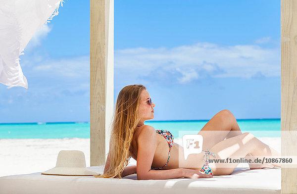 Junge Frau im Bikini  die auf einer Liege am Strand ein Sonnenbad nimmt  Dominikanische Republik  Karibik
