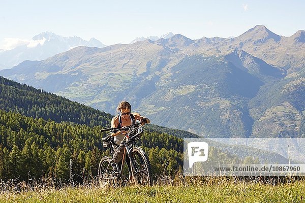 Female mountain biker pushing mountain bike uphill in landscape  Aosta Valley  Aosta  Italy