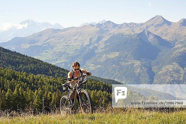 Female mountain biker pushing mountain bike uphill in landscape,  Aosta Valley,  Aosta,  Italy