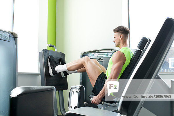Side view of young man in gym using exercise equipment