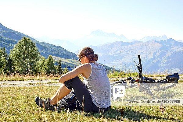 Mountainbikerin sitzt in Berglandschaft und liest Smartphone-Texte  Aostatal  Aosta  Italien