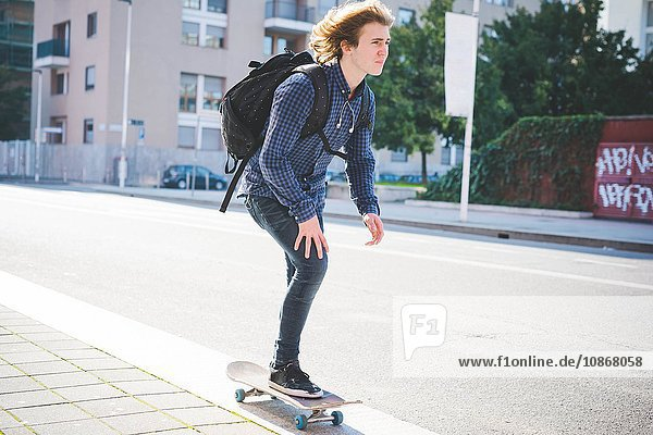 Junge männliche Skateboarder Skateboarder auf dem Bürgersteig