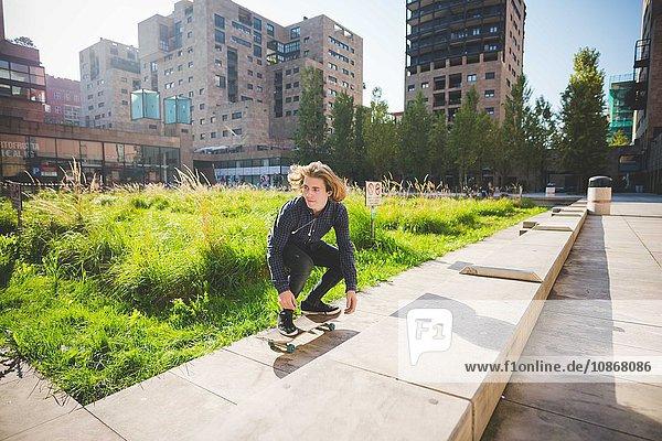Junge männliche Skateboarder hocken beim Skateboarden an der Stadtmauer