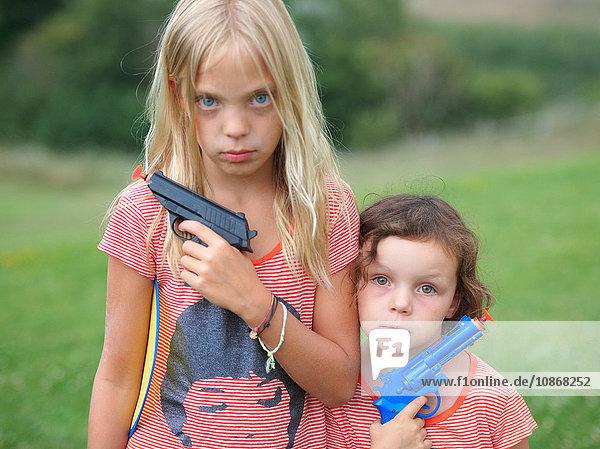 Porträt von zwei jungen Schwestern  die Spielzeugpistolen halten