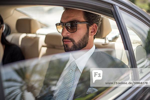 Young businessman wearing sunglasses in car backseat  Dubai  United Arab Emirates
