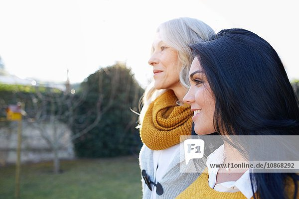 Women in garden arms around each other looking away smiling