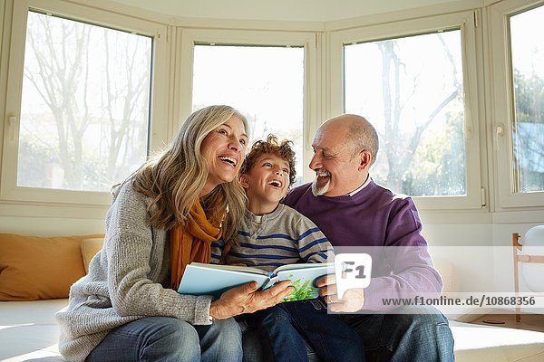 Grandparents on window seat reading book with grandson  smiling