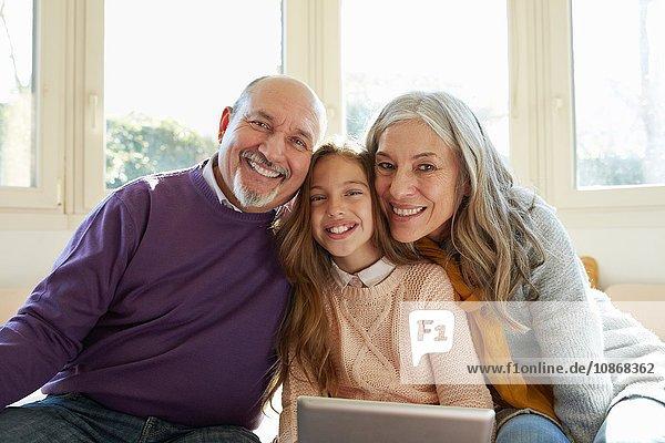 Großeltern am Fenster mit Enkelin  die ein digitales Tablett in der Hand hält und lächelnd in die Kamera schaut