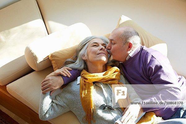 Hochwinkelansicht eines reifen Paares  das auf einem Fenstersitz liegt  Kuss auf die Wange