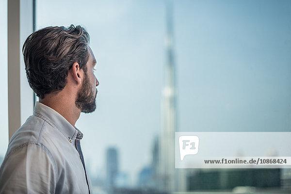 Geschäftsmann blickt durch Fenster mit Blick auf Burj Khalifa  Dubai  Vereinigte Arabische Emirate