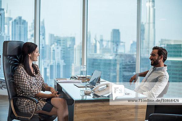 Geschäftsfrau und Mann am Schreibtisch mit Fensterblick  Dubai  Vereinigte Arabische Emirate