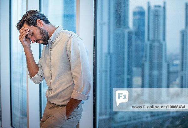 Geschäftsmann mit Hand auf der Stirn am Fenster mit Blick auf einen Wolkenkratzer  Dubai  Vereinigte Arabische Emirate