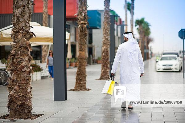 Rückansicht eines Mannes  der eine Dishdascha trägt und mit Einkaufstaschen durch die Straße läuft  Dubai  Vereinigte Arabische Emirate