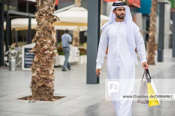 Mann in traditioneller Kleidung aus dem Nahen Osten geht mit Einkaufstaschen durch die Straße  Dubai  Vereinigte Arabische Emirate