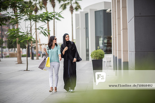 Junge Frau aus dem Nahen Osten in traditioneller Kleidung geht mit einer Freundin die Straße entlang  Dubai  Vereinigte Arabische Emirate