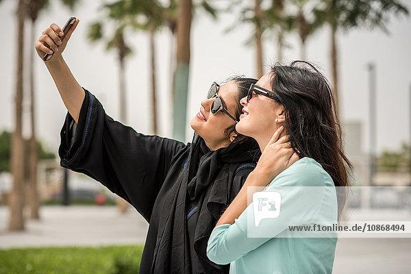 Junge Frau aus dem Nahen Osten in traditioneller Kleidung mit Smartphone-Selfie mit Freundin  Dubai  Vereinigte Arabische Emirate