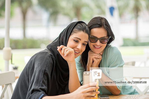 Junge Frau aus dem Nahen Osten in traditioneller Kleidung liest mit einer Freundin im Café einen Text auf einem Smartphone  Dubai  Vereinigte Arabische Emirate